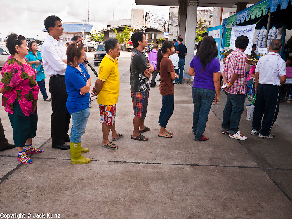 03 JULY 2011 - SAMUT PRAKAN, THAILAND:  People stand in line to vote in Samut Prakan, Thailand, Sunday, July 3. More than 47,000,000 Thais were registered to vote in Sunday's election, which had turned into a referendum on the current government, led, by the Thai Democrats and the oppositionPheu Thai party. Pheu Thai is the latest political incarnation of ousted Thai Prime Minister Thaksin Shinawatra. PT is led by his youngest sister, Yingluck Shinawatra, who is the party's candidate for Prime Minister. Exit polling by three Thai polling firms showed Pheu Thai winning a landslide election.      PHOTO BY JACK KURTZ