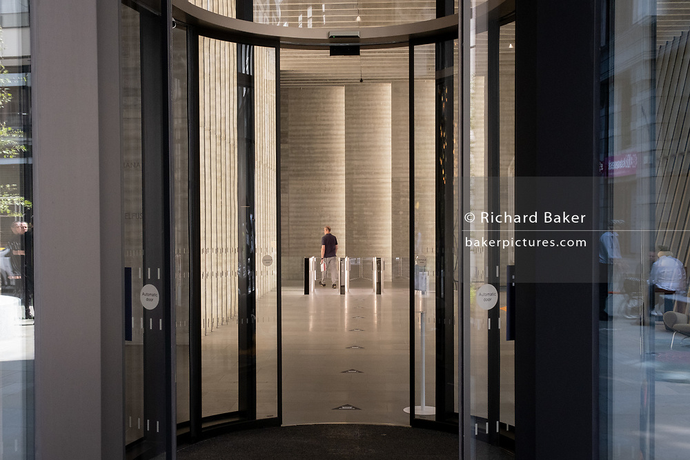 An employee of a City of London company walks through security barriers in the foyer of corporate office space, on 29th July 2020, in London, England.