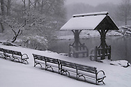 A view of Central Park including benches and a<br /> lakeside shelter during a snowstorm<br /> New York City   U.S.A. Winter in New York