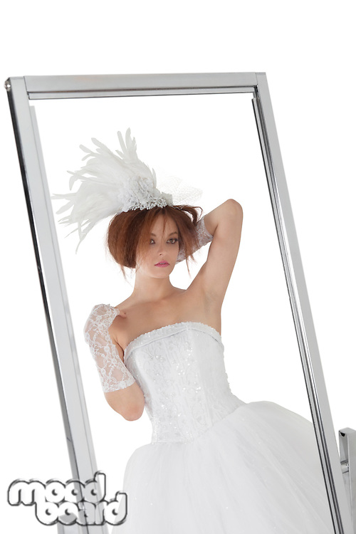 Reflection of young bride in mirror over white background
