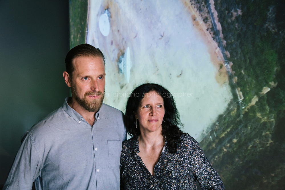 PALERMO, ITALY - 15 JUNE 2018: (R-L) Documentary director Laura Poitras and reporter Henrik Moltke pose for a portrait in front of their video installation &quot;Signal Flow&quot; (2018) at Palazzo Forcella De Seta during Manifesta 12, the European nomadic art biennal, in Palermo, Italy, on June 15th 2018.<br /> <br /> Manifesta is the European Nomadic Biennial, held in a different host city every two years. It is a major international art event, attracting visitors from all over the world. Manifesta was founded in Amsterdam in the early 1990s as a European biennial of contemporary art striving to enhance artistic and cultural exchanges after the end of Cold War. In the next decade, Manifesta will focus on evolving from an art exhibition into an interdisciplinary platform for social change, introducing holistic urban research and legacy-oriented programming as the core of its model.<br /> Manifesta is still run by its original founder, Dutch historian Hedwig Fijen, and managed by a permanent team of international specialists.<br /> <br /> The City of Palermo was important for Manifesta&rsquo;s selection board for its representation of two important themes that identify contemporary Europe: migration and climate change and how these issues impact our cities.