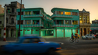 A green hotel building with the vehicles and a bicycle  on the Malecon in the evening.