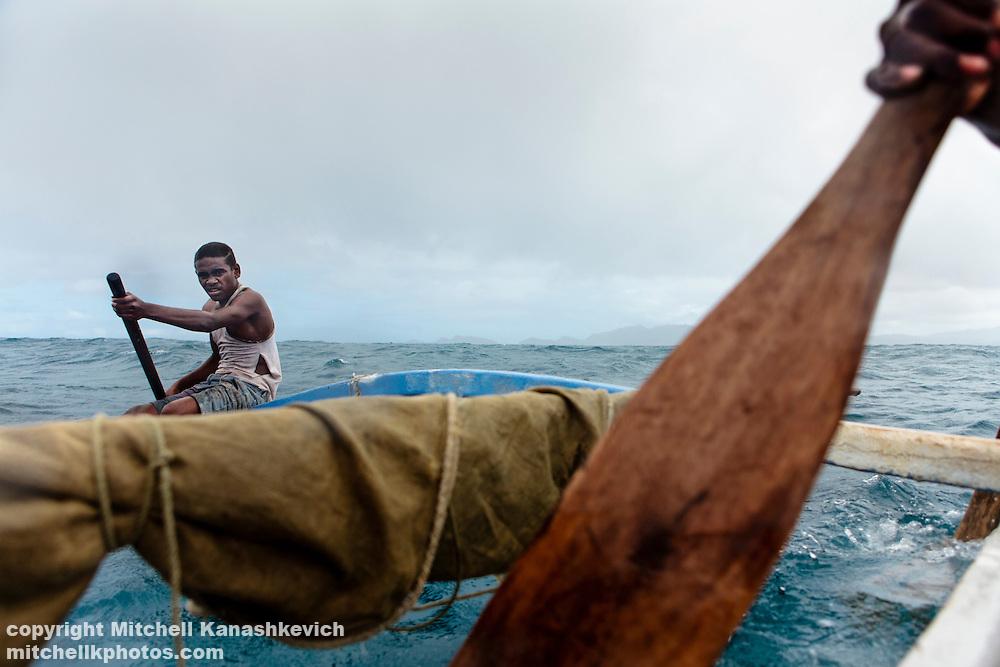 Teenage Ni Vanuatu boys paddling an outrigger canoe. Uleveo, Maskelyne Island, Malampa Province, Malekula, Vanuatu