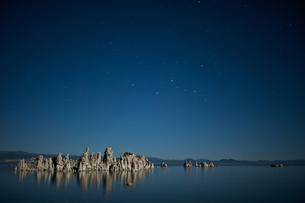 Tufa is a type of limestone that is formed when calcium-rich spring water mixes with the carbonate-rich Mono Lake water and precipitates around the spring. The towers grow underneath the waters surface. These towers were exposed when the city of Los Angeles diverted four of the five streams flowing into Mono Lake.  Deprived of its freshwater sources, the lake volume dropped by half, exposing nesting colonies of gulls to predation and again doubling the lakes salinity. The entire eco-system began to collapse. In response David Gaines formed the Mono Lake Committee, a citizens group that was formed to reverse this trend and save the lake. In 1994 the California Supreme Court mandated that the lake should rise to a level of 6,392 feet, which will partially restore the ecosystem and migratory bird habitat.<br /> <br /> This image shows South Tufa beneath moonlight.