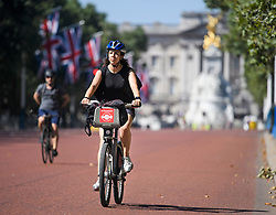 © Licensed to London News Pictures. 23/07/2018. London, UK. A woman rides her bike along The Mall in front of Buckingham Palace in early morning sun in central London, as the hot weather continues in the capital. Forecasters are predicting record temperatures this week. Photo credit: Ben Cawthra/LNP