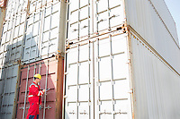 Male worker inspecting cargo containers while writing on clipboard in shipping yard