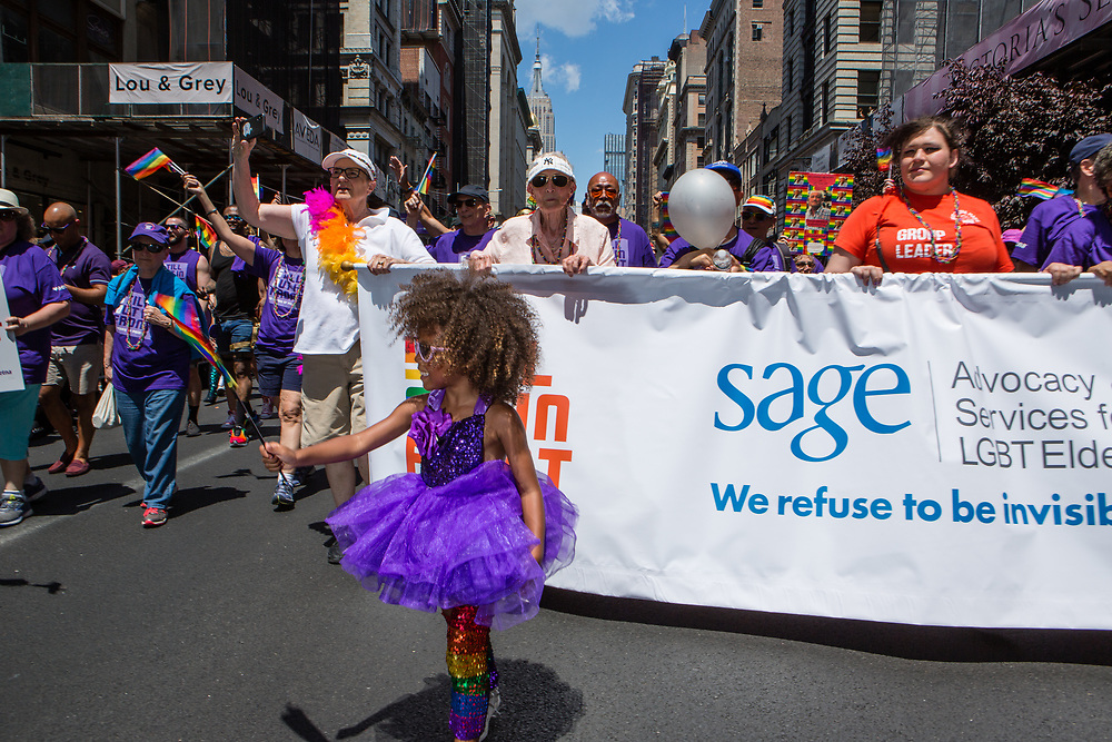 New York, NY - 30 June 2019. The New York City Heritage of Pride March filled Fifth Avenue for hours with participants from the LGBTQ community and it's supporters. A young girl wears a purple tutu and sparkly rainbow leggings, while Sage, which provides advocacy servics for LGBT elderly, march behind.