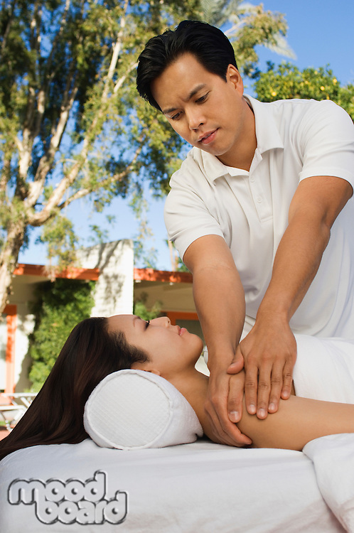 Massuese massaging young woman at health spa