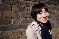 Portrait of a happy young Asian woman against wall