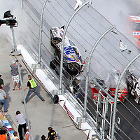 A horrific wreck of NASCAR driver Kyle Larson occurs with debris flying into the spectator grandstand area on the front stretch during a NASCAR Drive for COPD 300 race at Daytona International Speedway on Saturday, February 23, 2013 in Daytona Beach, Florida.  (AP Photo/Alex Menendez)
