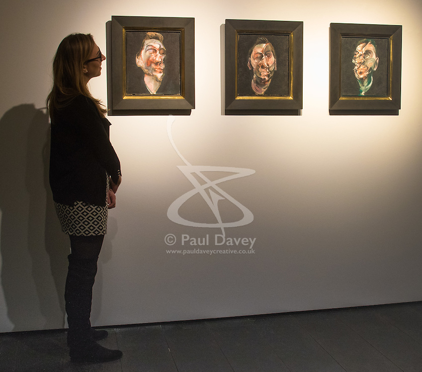Christie's, London, February 24th 2017. Fine art auctioneers Christie's hold a press preview for their Impressionist and Modern Art and Art of the Surreal sale which takes place on 28th February. PICTURED: A woman examines Three studies for a portrait of George Dyer, Francis Bacon's first ever portrait of his great muse, painted in 1963. The paintings were formerly in the collection of Roald Dahl and appear on the auction market for the first time, with they triptych expected to realise between £50-70million.