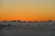 At twilight, sunset turns blue sky orange over ocean clouds, seen from Kalalau Lookout at 4000 feet above the Pacific Ocean. Koke'e State Park, island of Kauai, Hawaii, USA.