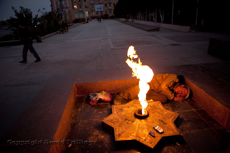 Intoxicated, a man sleeps next to the eternal flame on Victory Square in the Caspian port town of Turkmenbashi. Marking the win over Nazi Germany in WWII, the flame is almost holy in many post-Soviet countries.