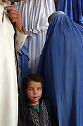 A young Afghan boy with his parents in a burqa shop in Kabul, Afghanistan. 2002.