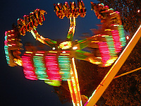 A brightly colored and fast-moving carnival ride at night.
