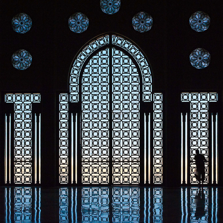 Man gazes out the ornate windows of the Hassan II mosque. The floor's reflection ripples like water.