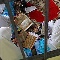 Malaysian Muslim women reads the holy Quran during the 'berendoi' ceremony in Kuala Lumpur, Malaysia. Berendoi is part of malay tradition in welcoming newborn baby.