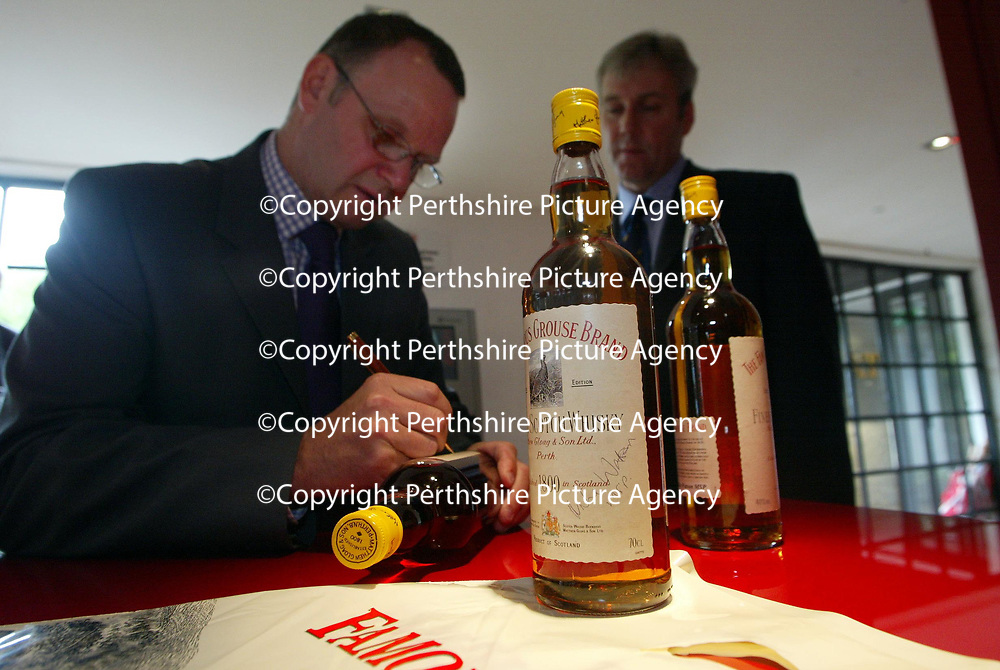 Mike Watson MSP Minister for Tourism who unveiled the giant copper grouse at The Famous Grouse Experience in Crieff to officially open the new visitor centre,signs a bottle of whisky watched by Derek Brown, Director TFGE<br />