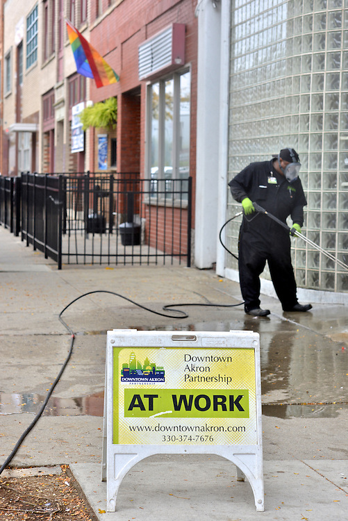 A Downtown Akron Partnership cleaning & safety ambassador power washing the sidewalks.