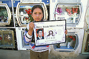 A girl, standing in the cemetery of Oruro, Bolivia, at Todos Santos, holds up a picture with a photograph and the name of her dead father. In the Altiplano of Bolivia, it is customary that a family, in which there has been a death within the last three years, call down the spirit for a three day visit at Todos Santos. On the third day, when the spirit leaves the home, the families go to the cemeteries to decorate the graves and say farewell to the soul of the dead.