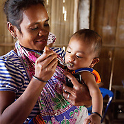 61/2 months Marcolina is fed mashed rice with bananas by her mother Maria as part of  a Mother Support Group session where breast feeding mothers with 4 months plus babies learn about food supplements. Maria has bee doing .exclusive breast feeding but has started complimentary feeding. She cooks rice and veggies and beans. .She is a member of mother's support group where they share knowledge. Every month she visits house holds of pregnant women to give advice. Her husband is a farmer, he grows veggies and sell some and feed the family as well. Maria has been trained by Alola, she understands the importance of nutritious food but its her first attendants at this workshop. She has got 4 other children, oldest is 12.  .Infant mortality rates are very high in Timor-Leste and one of the reasons for that is poor nutrition. Alola advocate breast feeding till at least two years old and teach women about nutritious supplements such as boiled and mashed rice w vegetables and eggs.  Fundasaun Alola is a not for profit non government organization operating in Timor Leste to improve the lives of women and children. Founded in 2001 by the then First Lady, Ms Kirsty Sword Gusmao, the organization seeks to nurture women leaders and advocate for the rights of women.