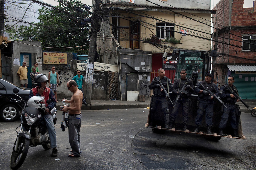Police members of BOPE special forces rides on a bulldozer by residents during an incursion by security forces into 'Rocinha', one of Brazil's biggest slums controlled by drug traffickers, on November 13, 2011, Rio de Janeiro, Brazil. Photo by Mauricio Lima for The New York Times