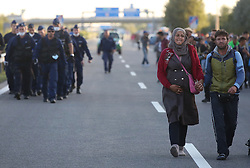 © London News Pictures. Migrants walk along the motorway towards Budapest after they  broke out from the camp close to the Hungarian and Serbian border town of Roszke, Hungary, September 7 2015. The UN's humanitarian agencies are on the verge of bankruptcy and unable to meet the basic needs of millions of people because of the size of the refugee crisis in the Middle East, Africa and Europe, senior figures within the UN have told the media.   Picture by Paul Hackett /LNP