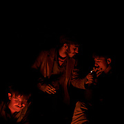 Afghan boys sit around a fire after a long day scavenging for recyclables at a garbage dump site in the outskirts of Kabul.