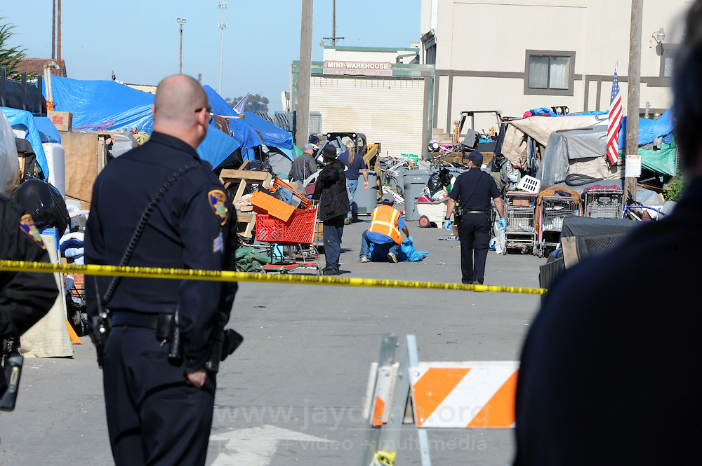 Under police guard and roped-off streets, workers hired by the city of Salinas clean out homeless encampments in the Market Way area of Chinatown.