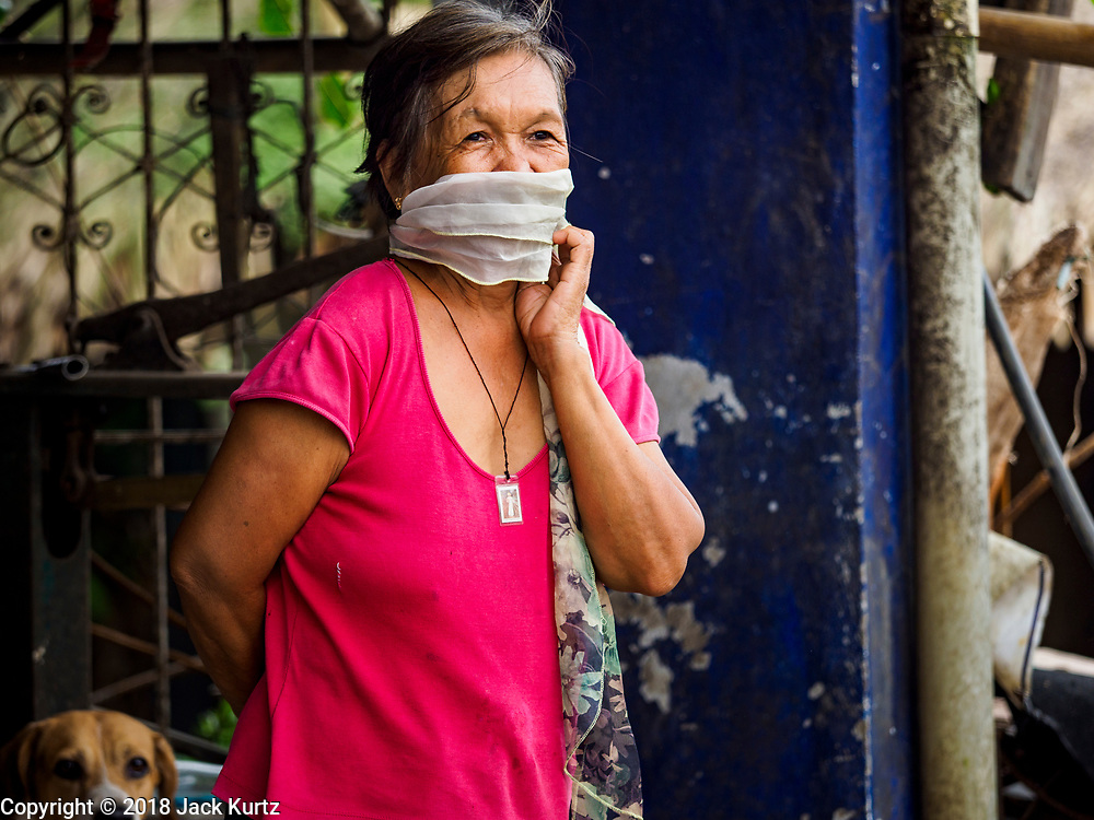 "22 JANUARY 2018 - GUINOBATAN, ALBAY, PHILIPPINES: A woman in Guinobatan wears a face mask because of an ash fall caused by the eruption of Mayon volcano. Several communities in Guinobatan were hit ash falls from the eruptions of the Mayon volcano and many people wore face masks to protect themselves from the ash. There were a series of eruptions on the Mayon volcano near Legazpi Monday. The eruptions started Sunday night and continued through the day. At about midday the volcano sent a plume of ash and smoke towering over Camalig, the largest municipality near the volcano. The Philippine Institute of Volcanology and Seismology (PHIVOLCS) extended the six kilometer danger zone to eight kilometers and raised the alert level from three to four. This is the first time the alert level has been at four since 2009. A level four alert means a ""Hazardous Eruption is Imminent"" and there is ""intense unrest"" in the volcano. The Mayon volcano is the most active volcano in the Philippines. Sunday and Monday's eruptions caused ash falls in several communities but there were no known injuries.    PHOTO BY JACK KURTZ"