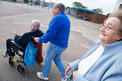 Wheel chair user and wife being helped by a friend  whilst on a day trip to Skegness organised by Nottingham Disabled Friendship Club, ,