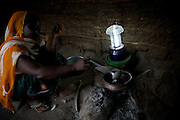 Sofia Mnandi uses the light from her solar lantern to cook in the evening at her home in Chekeleni village, near Mtwara, Tanzania...Sofia trained as a solar engineer as part of the innovative Barefoot Solar project which enables women from the poorest communities in rural Tanzania to run successful businesses by installing, repairing and maintaining solar equipment for their communities and beyond...VSO volunteer Lesley Reader project manages the scheme by liaising with the Tanzanian government, Barefoot college and the Indian government.