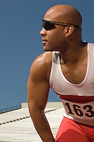 Runner with sunglasses on a track