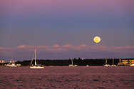 A sailboat cruises through Miami harbor towards the Port of Miami, as the full moon rises over Virginia Key in the background.<br />