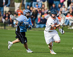 Virginia midfielder Brian Mcdermott (26) runs past Johns Hopkins midfielder Michael Powers (5).  The #2 ranked Virginia Cavaliers defeated the #6 ranked Johns Hopkins Blue Jays 13-12 in overtime at the University of Virginia's Klockner Stadium in Charlottesville, VA on March 22, 2008.  The loss, in front of a record UVA crowd of 7,500, was the third consecutive overtime defeat for Hopkins, the defending national champions.