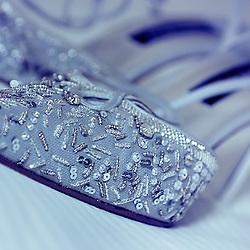 Wedding pumps rest on bedspread.