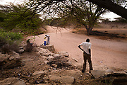 Collecting water from a well tapping into a river bed during an expedition into Northern Kenya.
