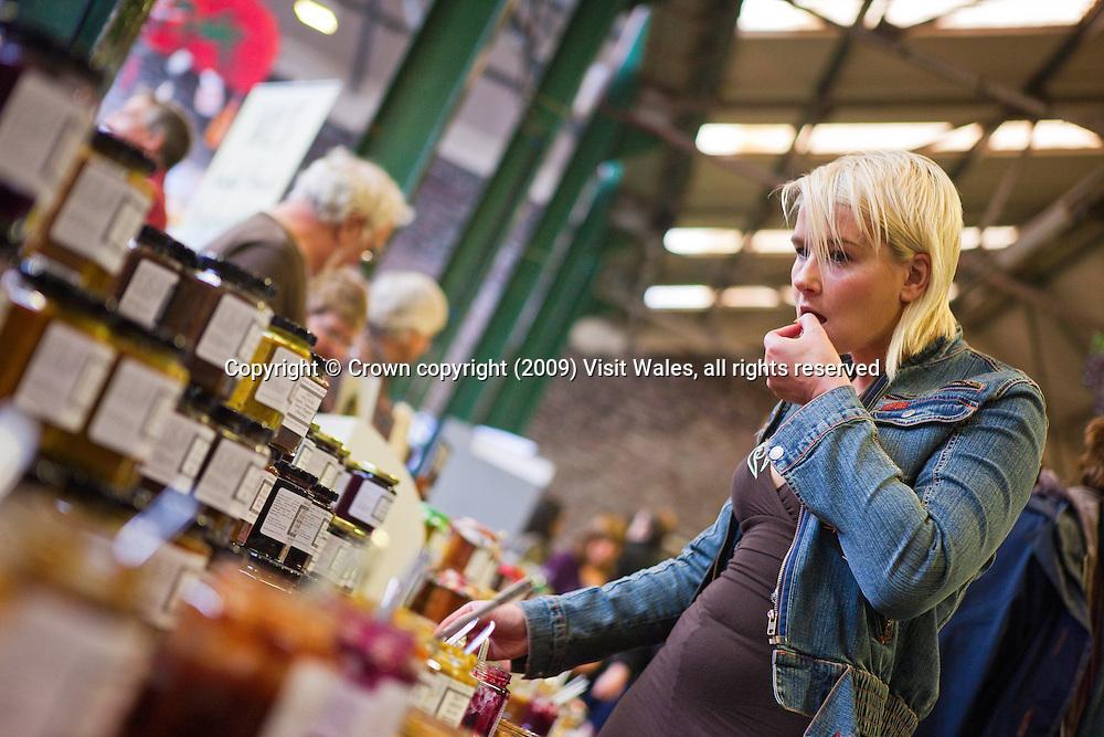 Woman sampling produce<br /> Brecon Food Festival 2009<br /> Market Hall<br /> Brecon<br /> South<br /> Food
