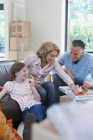 Parents and daughter (7-9) eating pizza in new home