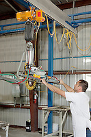Industrial worker adjusting machinery in factory