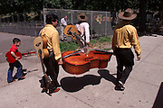Traditional Mexican musicians carry their instruments in the Mott Haven section of the South Bronx.