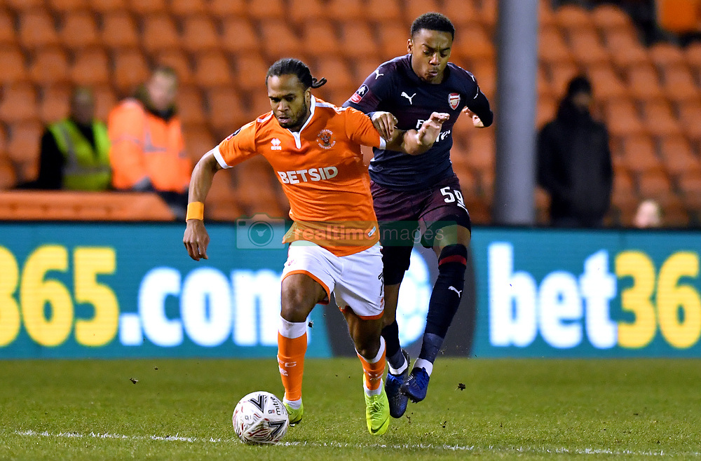 Blackpool's Nathan Delfouneso's (left) and Arsenal's Joe Willock battle for the ball during the Emirates FA Cup, third round match at Bloomfield Road, Blackpool.