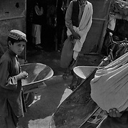 Young boys with wheelbarrows sit in front of shops selling produce in the Afghan border town of Wesh in Spin Boldak District, Kandahar Province, Afghanistan.  As a buslting border town this border crossing connected to Kandahar City via Highway 4 sees millions of dollars of trade pass through it's streets most of which goes to rich warlords and corrupt government officials. These boys with the wheelbarrows can be hired to move goods and luggage cheaply in small amounts across the border with no passport required..(Credit Image: © Louie Palu/ZUMA Press/The Alexia Foundation).August 25, 2010.Photograph taken on film exact date estimated and not known.....
