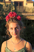 Pretty smiling young woman with red bougainvillea flowers in her hair, Lliber, Marina Alta, Alicante province, Spain