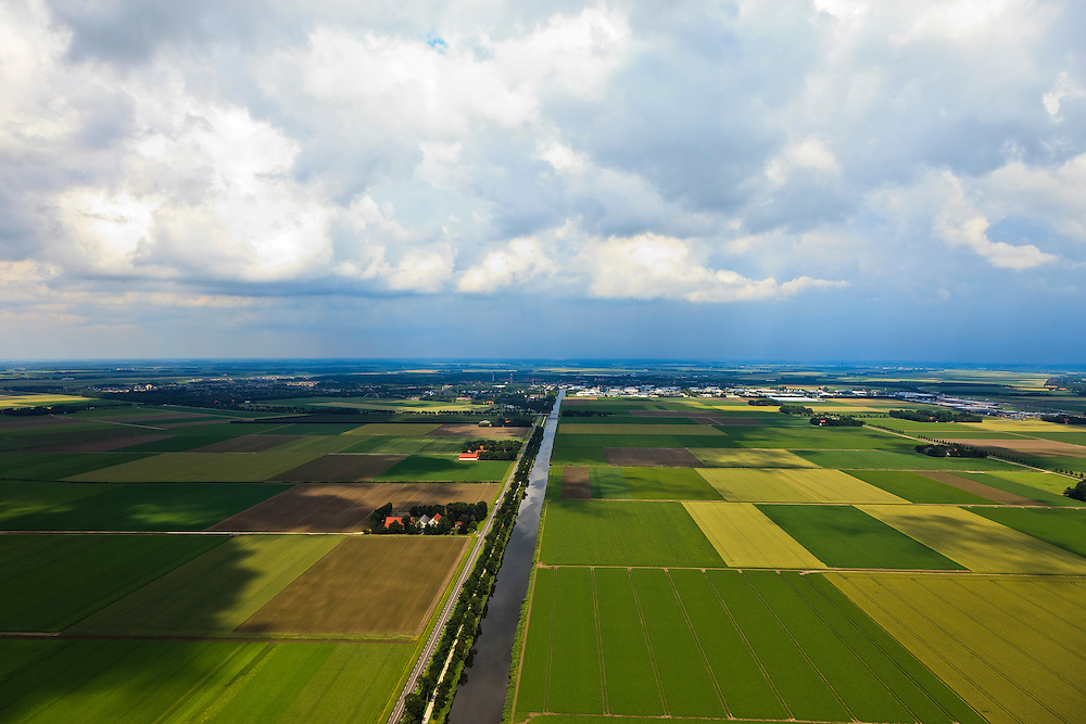 Nederland, Noordoostpolder, 30-06-2011; Urkerweg (Emmeloord aan de horizon). De Noordoostpolder (NOP), is een voorbeeld van moderne grootschalige polder met rationele verkaveling. De aanleg van de polder maakte  deel uit van de Zuiderzeewerken (plan Lely) en viel in 1942 droog. De meeste boerderijen (en dorpen) zijn van na de tweede wereldoorlog..The northeast polder (NOP), is an example of modern large-scale polder with rational allotment. The construction of the polder was part of the Zuiderzee Works (Lely plan), in 1942 the polder was dry. Most of the building, farmhouses and villages, is post-war..luchtfoto (toeslag), aerial photo (additional fee required).copyright foto/photo Siebe Swart
