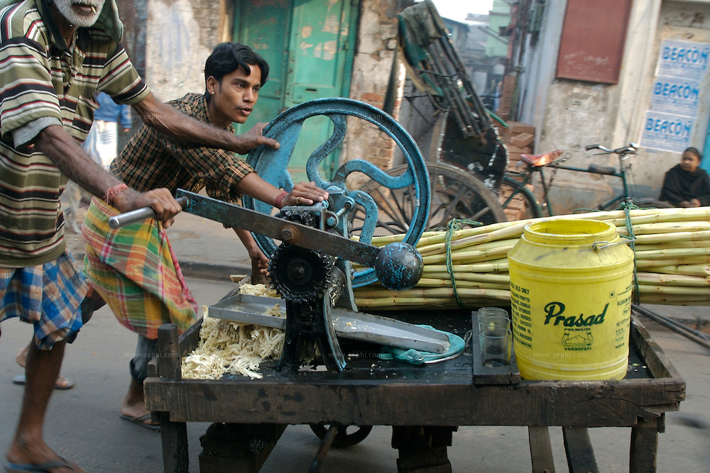 Two men puch a sugar-cane juice (Ganna, or Ankh in Bangla) cart in Kolkata, January 2007