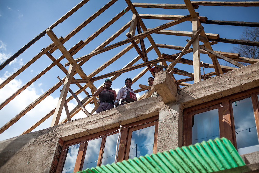 A group of Roma men reconstructing a roof top in the city of Crnik, Macedonia.