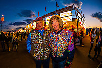 A man and woman wearing jackets covered in souvenir balloon pins, Balloon Fiesta Park, Albuquerque International Balloon Fiesta, Albuquerque, New Mexico USA.