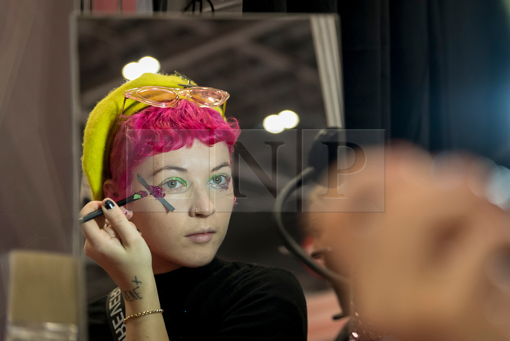 © Licensed to London News Pictures. 25/02/2019. LONDON, UK. A woman applies glitter to her face at Professional Beauty, the UK's largest beauty and spa trade show, taking place at Excel London in Docklands.  Photo credit: Stephen Chung/LNP