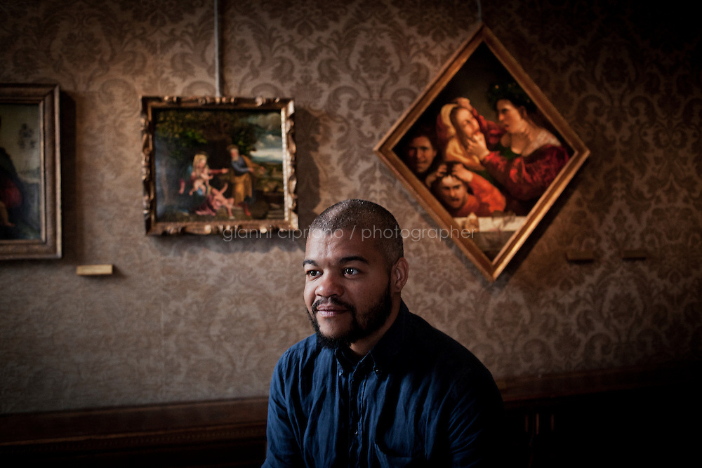 VENICE, ITALY - 1 JUNE 2013: Angolan artist Edson Chagas, 36, poses in the space of &quot;Luanda, Encyclopedic City&quot;, composed of his 23 large-format photographic poster, at Palazzo Cini in Venice, Italy, on June 1st 2013. <br /> <br /> &quot;Luanda, Encyclopedic City&quot; is the First Pavilion of the Republic of Angola at the 55th International Art Exhibition - la Biennale di Venezia and the first African Pavilion that wins the Golden Lion.<br /> <br /> Angolan artist Edson Chagas focuses on the complexity of Angola's capital, Luanda, which derives from the presence of unpredictable spaces and the coexistence of irreconcilable programs: city and country, infrastructure and habitations, garbage tips and public spaces. Luanda is an encyclopedic city.<br /> <br /> The 55th International Art Exhibition of the Venice Biennale takes place in Venice from June 1st to November 24th, 2013 at the Giardini and at the Arsenale as well as in various venues the city. <br /> <br /> Gianni Cipriano for The New York TImes